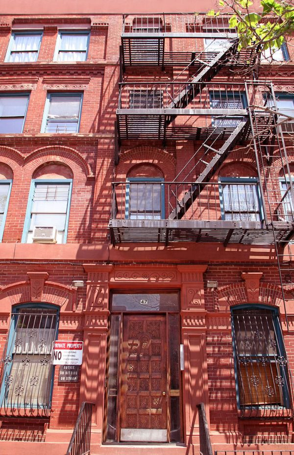 A photo looking up at the red brick building at 47 Clifton Place, Brooklyn, NY