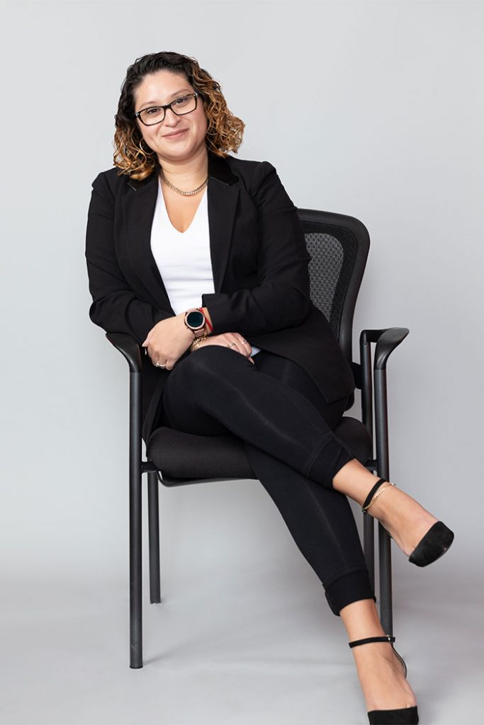 Eileen Jimenez smiles while leaning left in a chair